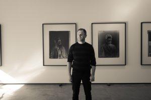The artist Jon Rotman in front of his images of Renata Kawepo (left) and Tareha Te Moanannui.